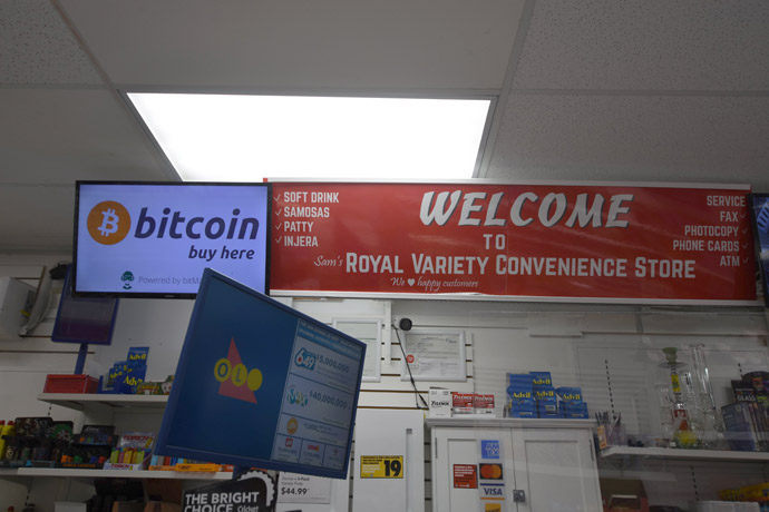 Inside the store: we see a lottery screen, a 'Welcome to Royal Variety Convenience Store' panel and 'Bitcoin - Buy here' TV screen