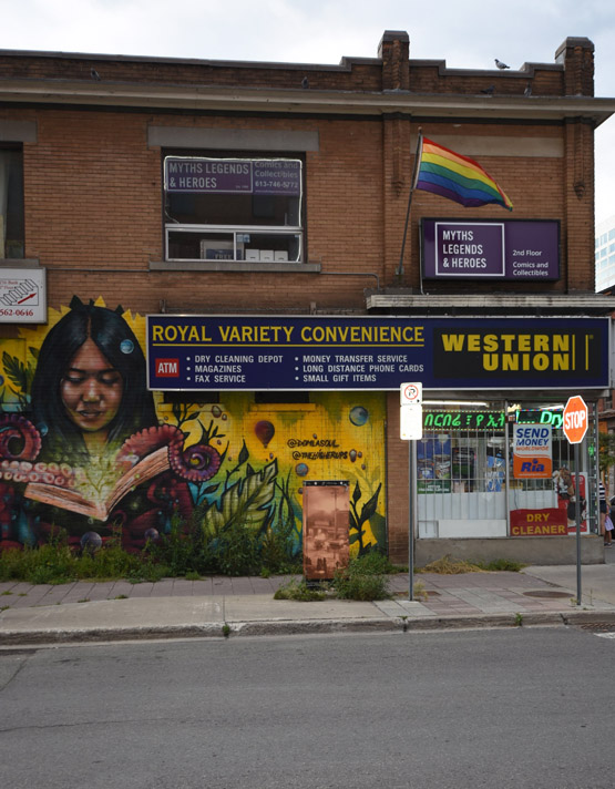 Outside view of the Royal Variety Convenience where we see a beautiful mural and a LGBT flag