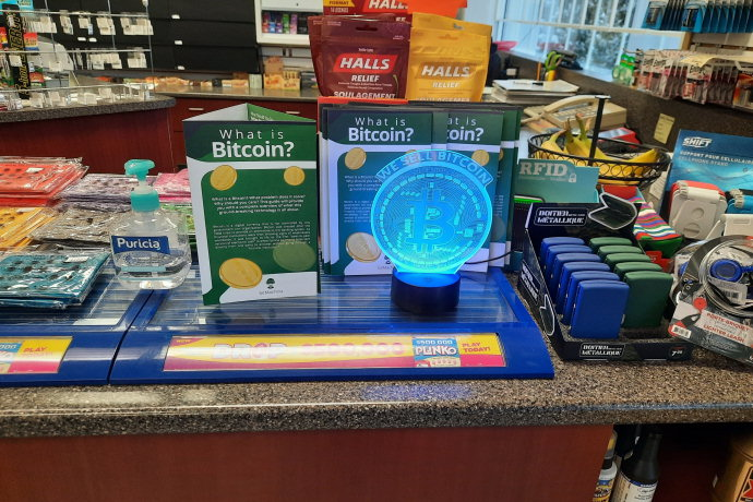 Counter of the store: we see a 'WE SELL BITCOIN' lamp and brochures