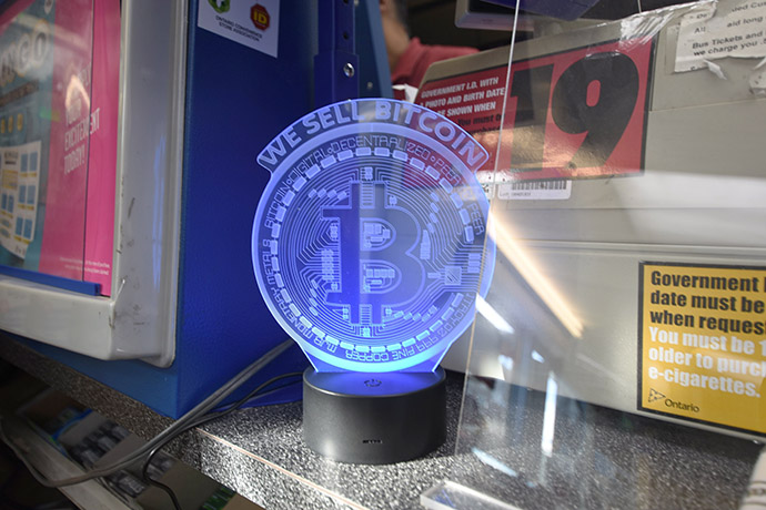 Cashier counter with a 'WE SELL BITCOIN' lamp