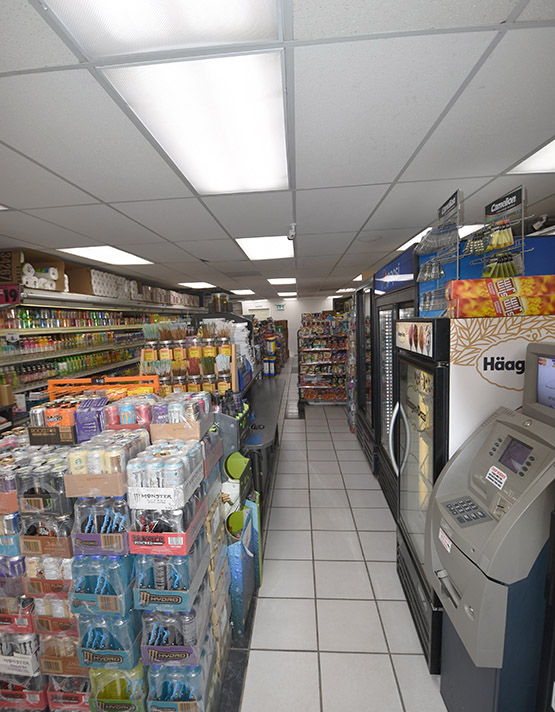 Inside the store: an alley where you can see many drinks and a cash ATM