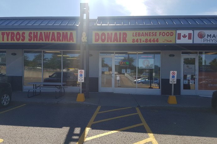 Outside view of Tyros Shawarma store with empty parking spaces